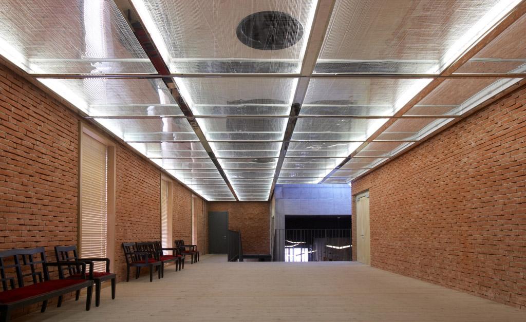 Il luminoso spazio del Foyer, caratterizzato da una sequenza di finestre che si affacciano sulla piscina.